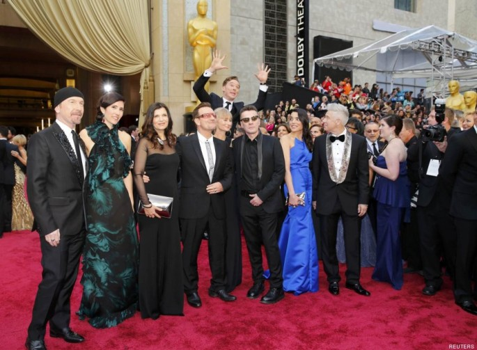 Actor Benedict Cumberbatch jumps behind U2 at the 86th Academy Awards in Hollywood