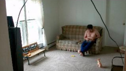 Picture of the living room. A guy in jeans and no shirt is on the couch. Also a chihuahua.