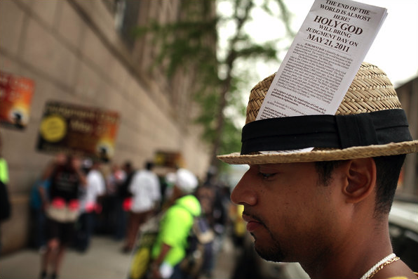 A man on the street in New York with a pamphlet warning of judgment day in his hat.