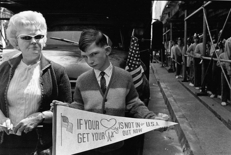 "Crazy looking kid holding a banner that reads ""If you're heart is not in the USA, get your ass out now."" Circa 1960."
