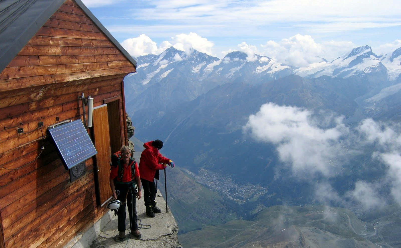 Picture of 2 men standing outside a mountain hut with a 3-foot ledge outside the front door.
